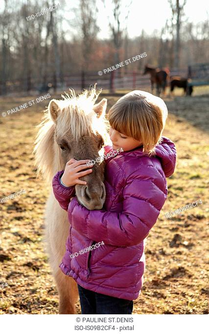 Young girl outdoors, hugging pony