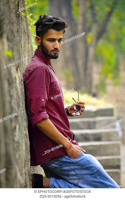 Young man with checked shirt with sun glasses in hand resting on a tree trunk, Pune, Maharashtra, India