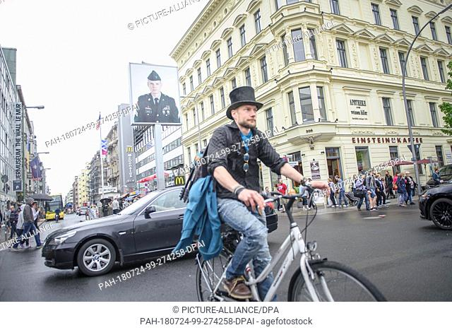 23 April 2018, Germany, Berlin: Juha Jaervinen, participant of the experiment Basic Income in Finland, rides past Checkpoint Charlie on a rented bike