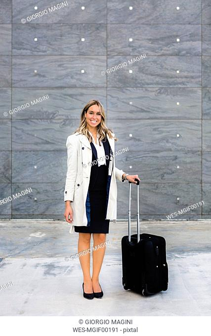Portrait of smiling businesswoman with suitcase wearing trench coat