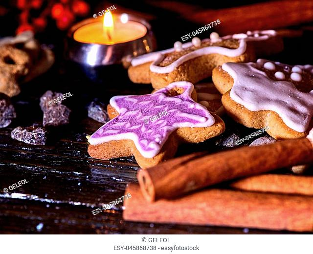 Cinnamon stick background with Christmas gingerbread man and star cookies are on wooden table and burning candles