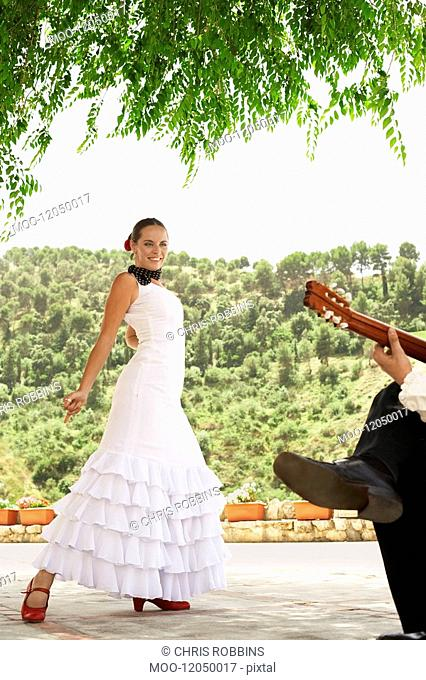 Woman flamenco dancing with man playing guitar