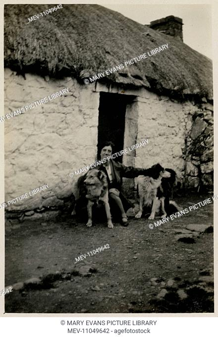 Woman outside a croft in Scotland with two collie dogs