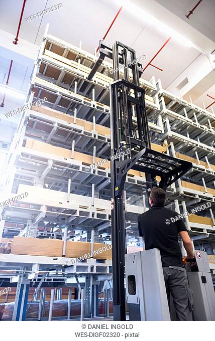 Worker operating forklift in factory warehouse
