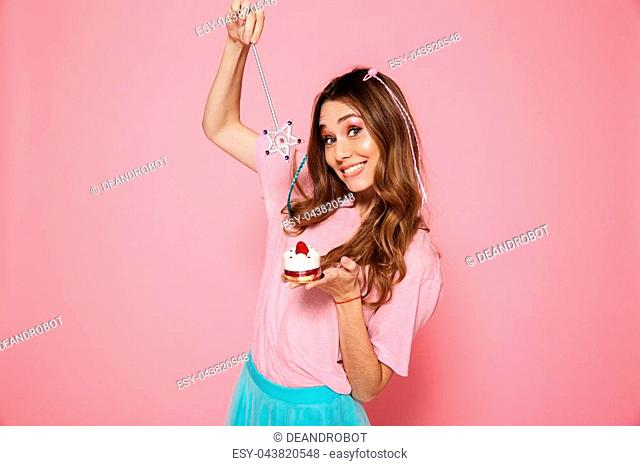 Close-up portrait of young smiling woman dressed as princess pointing with magic wand on cupcake, looking at camera, isolated on pink background