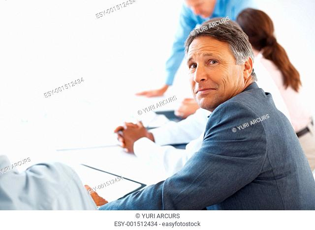 Portrait of smart mature business man sitting with his colleagues during meeting