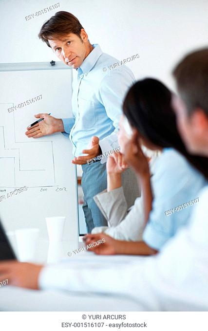 Portrait of a successful young businessman giving presentation to his colleagues at office
