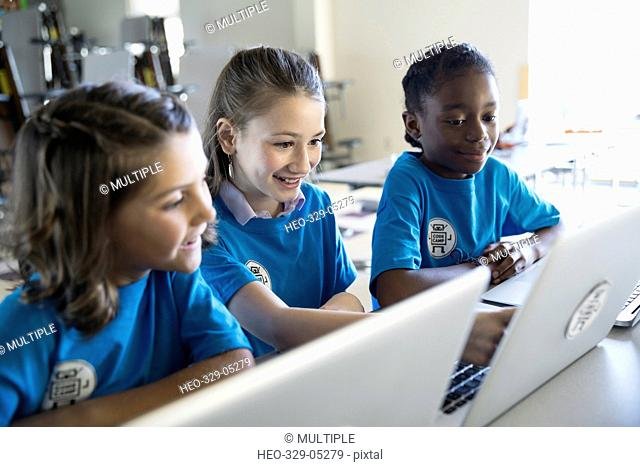 Pre-adolescent girls using laptops in classroom