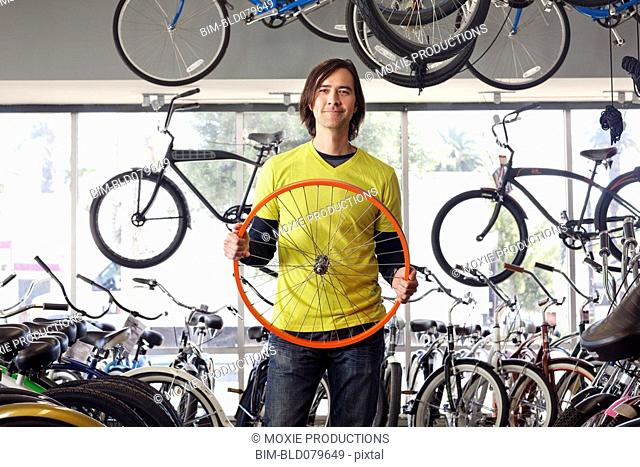 Mixed race bike shop owner holding bicycle tire