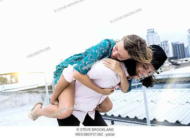 Young affectionate couple having fun together on rooftop