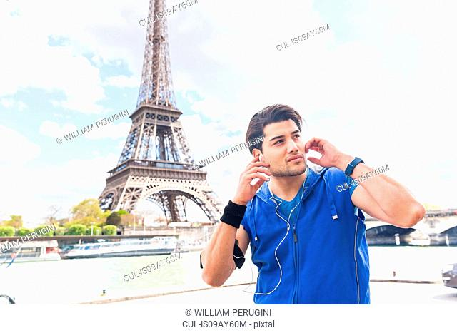 Young man taking a break from exercise, wearing earphones, Eiffel Tower in background