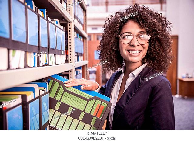 Young businesswoman removing file from office shelves