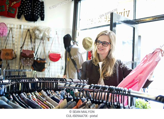 Young woman looking at pink shirt in vintage clothes shop