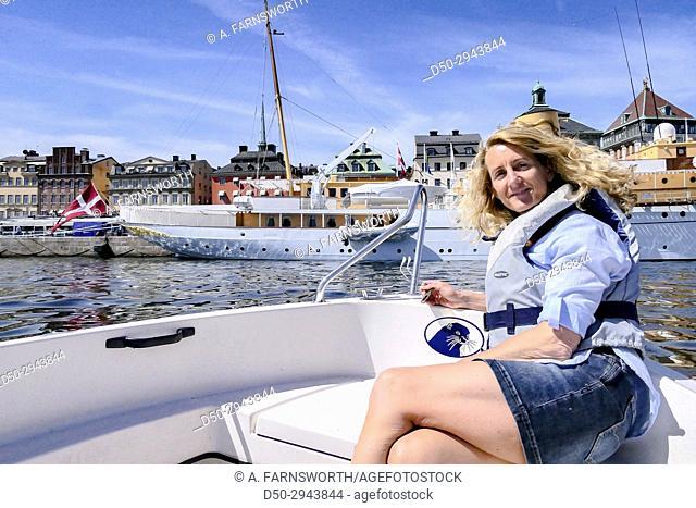 STOCKHOLM, SWEDEN Woman on motorboat next to the Danish Royal Yacht