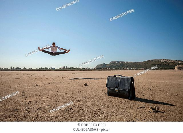 Mid adult businessman jumping mid air at beach