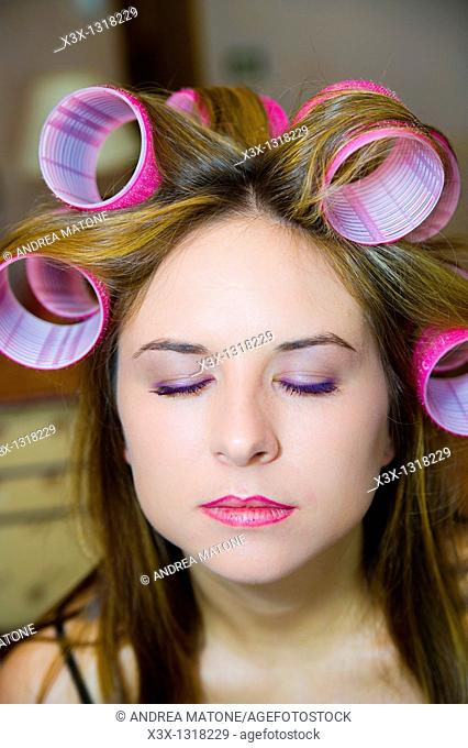 Woman's hair on curlers with eyes closed