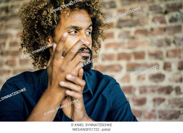 Man with beard and curly hair looking sideways