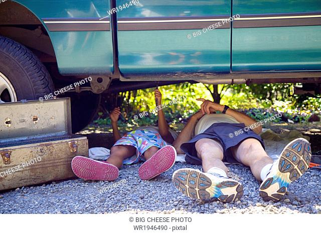 Man and a boy lying under a vehicle with a toolbox, doing repairs