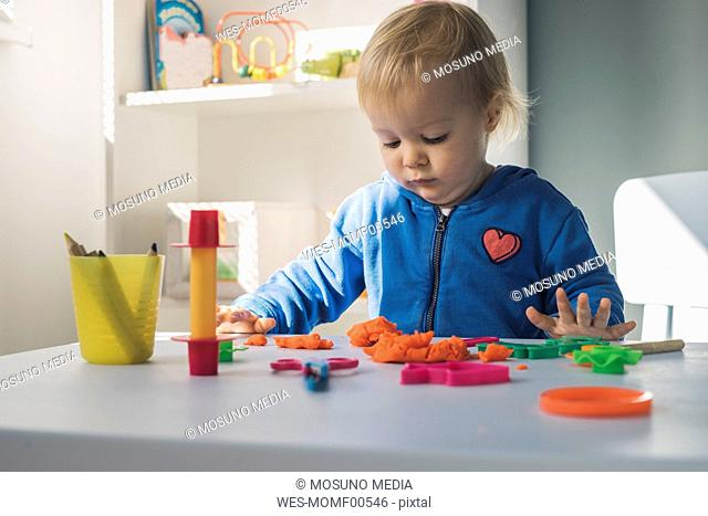 Portrait of baby girl playing with modeling clay