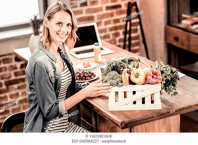 Healthy food. Positive delighted nice woman sitting in front of the box with vegetables and smiling while being at home