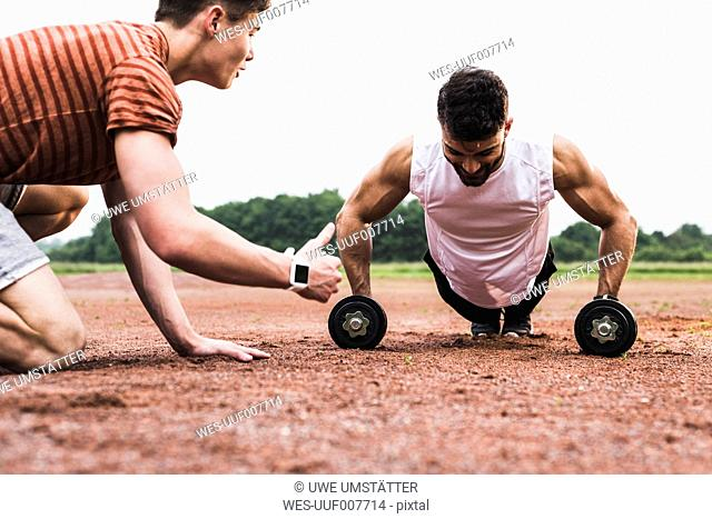 Athlete doing pushups with dumbbells on sports field supported by his training partner
