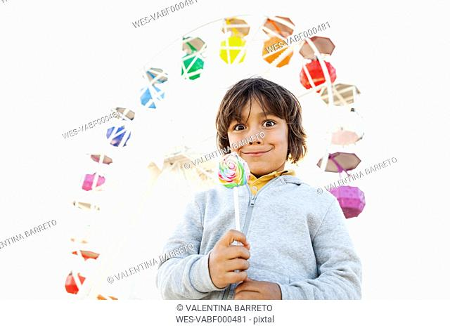 Portrait of little boy with lollipop pulling funny faces in front of big wheel