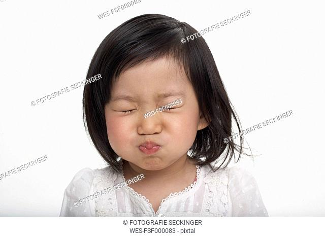 Little Asian girl holding breath, studio shot