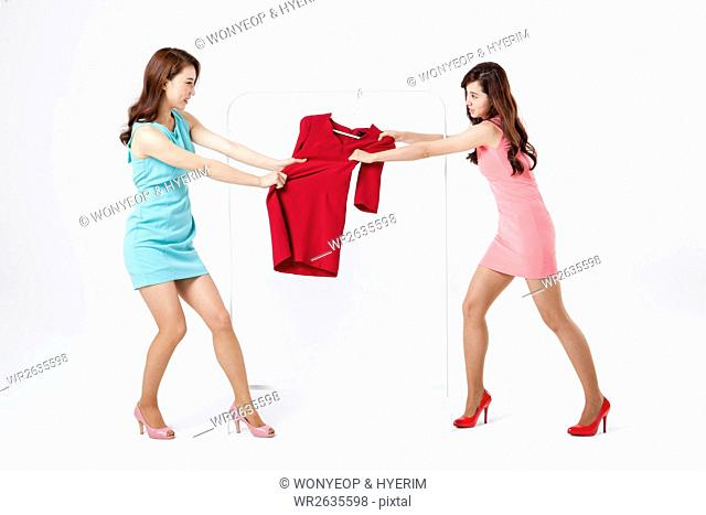 Two young women fighting for a dress