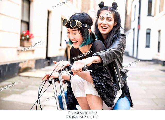 Two young stylish women cycling retro bicycle along street