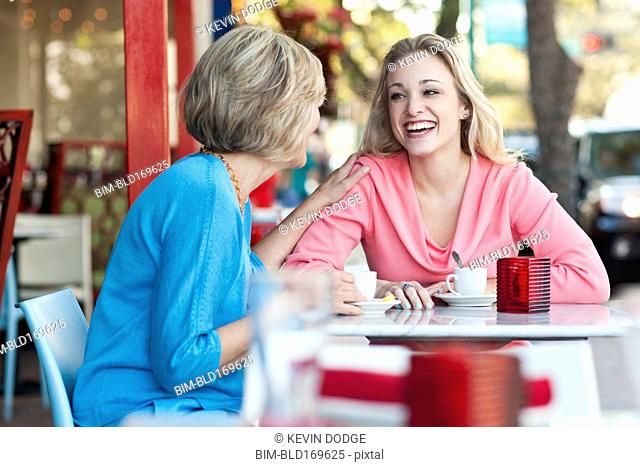 Caucasian mother and daughter drinking coffee at sidewalk cafe