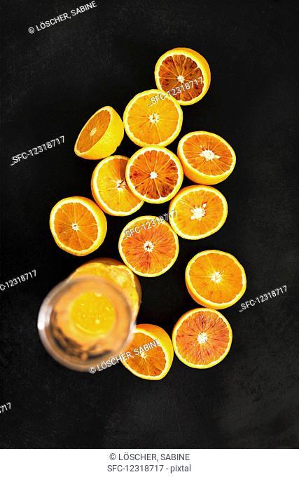 A glass jug of orange juice and halved Moro oranges against a black background