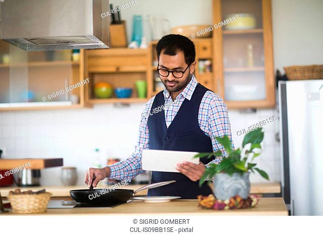 Man cooking while using digital tablet at home