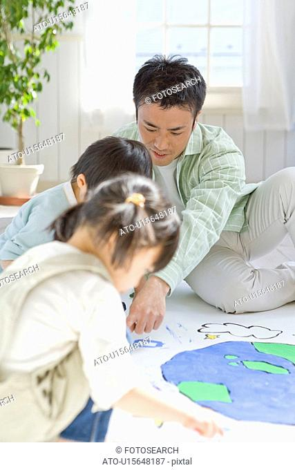 Boy and Girl Drawing Globe with Father