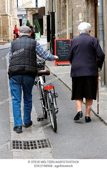An elderly couple walks through the streets of Pezenas, France