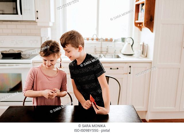 Children playing cards in kitchen