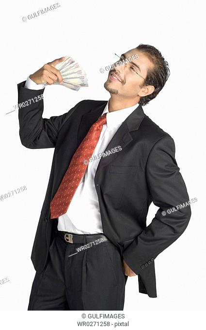 Businessman holding money, smiling