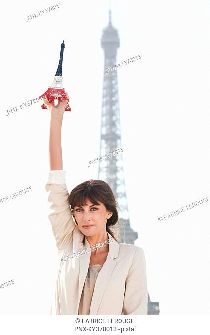 Woman holding a replica of the Eiffel Tower in front of the original one, Paris, Ile-de-France, France