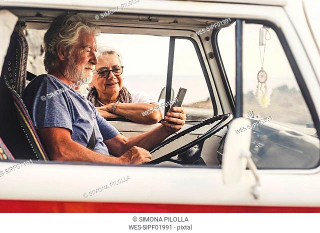 Senior couple traveling in a vintage van, using smartphone