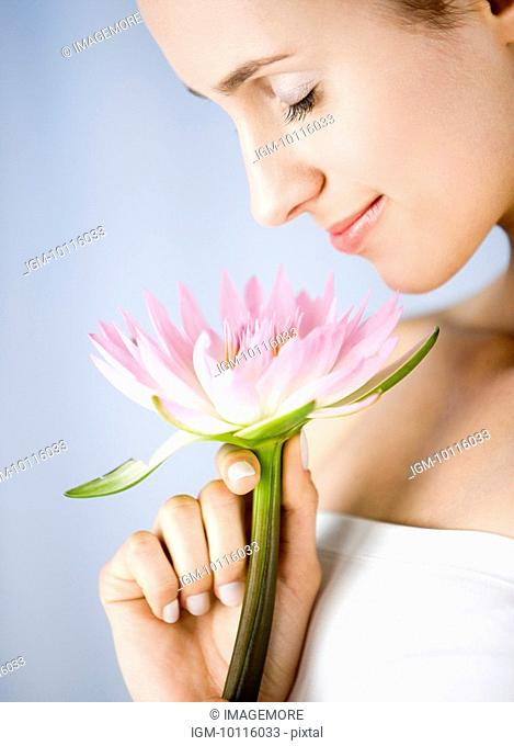 Close-up of young woman holding a lotus and closing her eyes