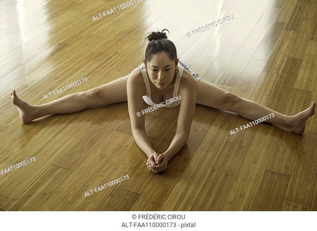 Woman stretching legs on floor
