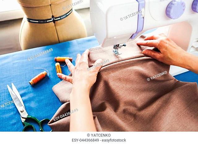Woman tailor working on sewing machine. Hands. close up. Tailoring. Details. Close up, vintage toned
