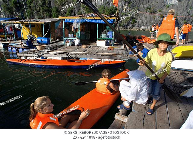 Tourists in Several Kayaks from a Tour Boat in Halong Bay Vietnam. Racers paddling sea kayaks in Halong Bay during an adventure race in Vietnam