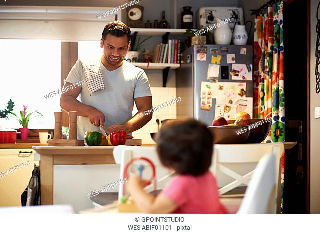 Smiling father preparing food for his daughter in kitchen at home