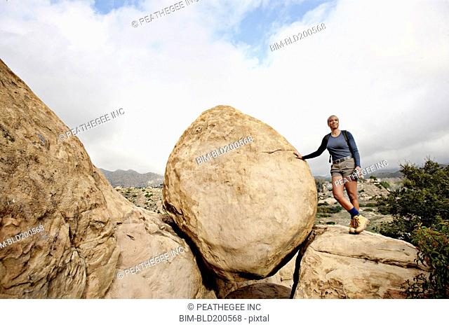 Black woman leaning against rock