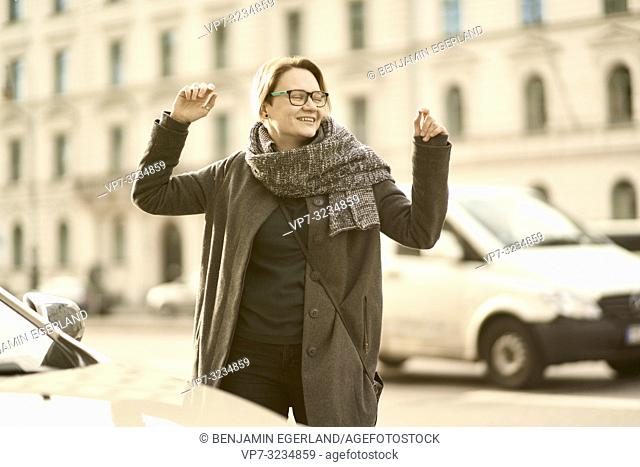 happy woman with arms up at street in city Munich, Germany