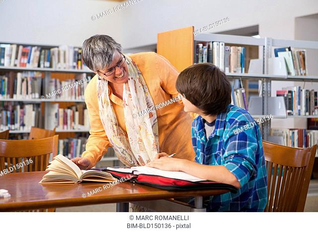 Librarian helping student in library