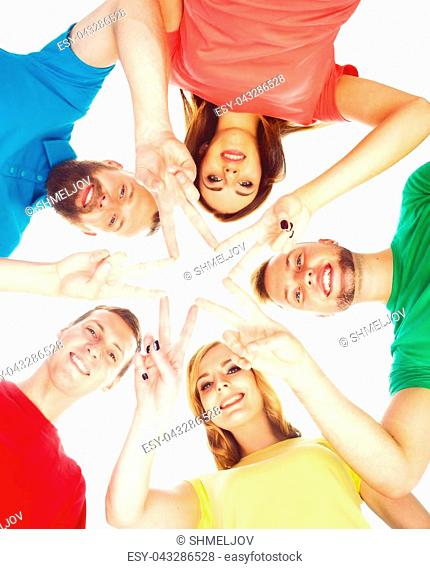 Happy students in colorful clothing standing together making star with their fingers