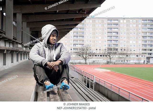 Man sitting on stadium bench
