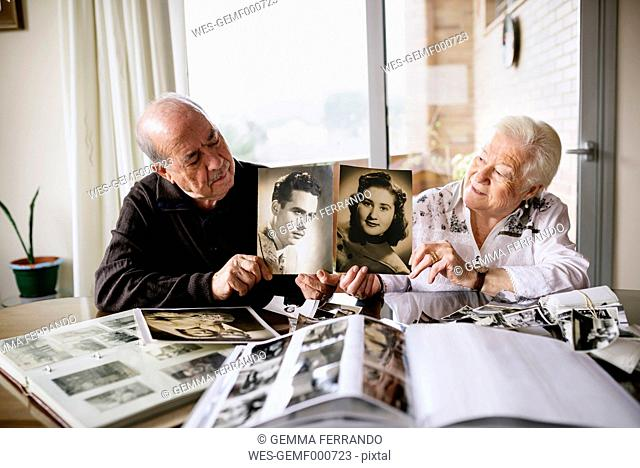 Senior couple showing old pictures of themselves
