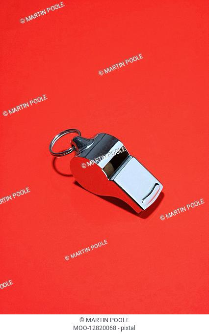 Whistle on red background in studio